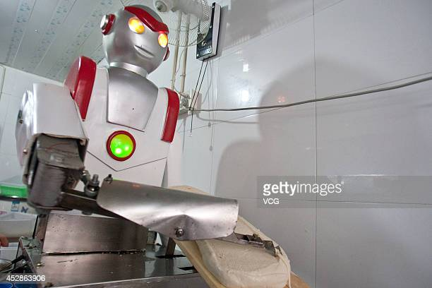A robot dressed as superman 'Ultraman' slices noodles at a restaurant on July 13 2012 in Hangzhou Zhejiang Province of China The restaurant owner...