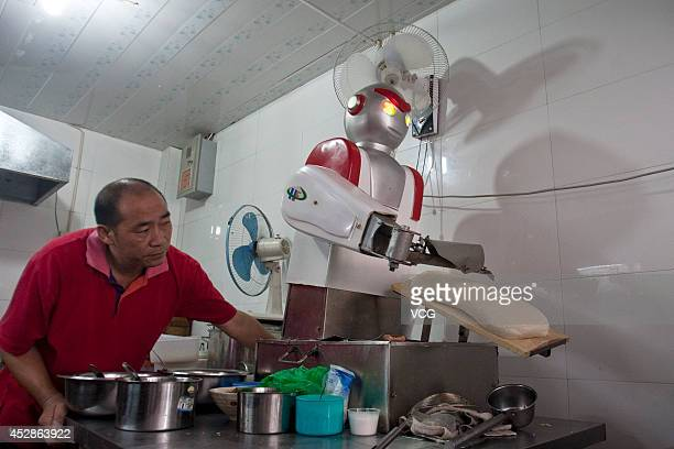 """Robot dressed as superman """"Ultraman"""" slices noodles at a restaurant on July 13, 2012 in Hangzhou, Zhejiang Province of China. The restaurant owner..."""