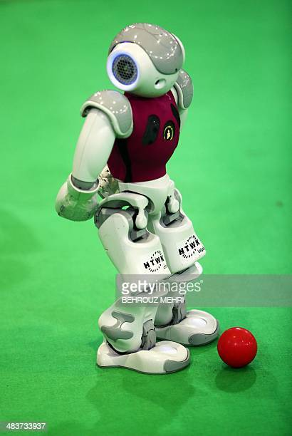 A robot from German NaoTeam HTWK of the Leipzig University of Applied Sciences takes part in a football game against 'Dutch Nao Team' from the Van...