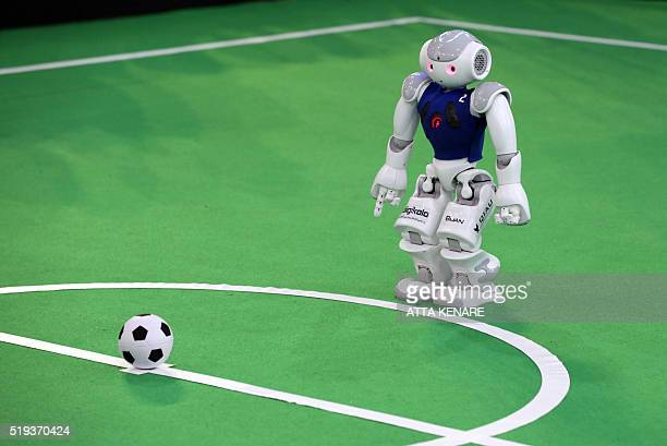 A robot from Iran's Qazvin Islamic Azad University takes part in a football match against Germany's NaoTeam HTWK of Leipzig United University during...