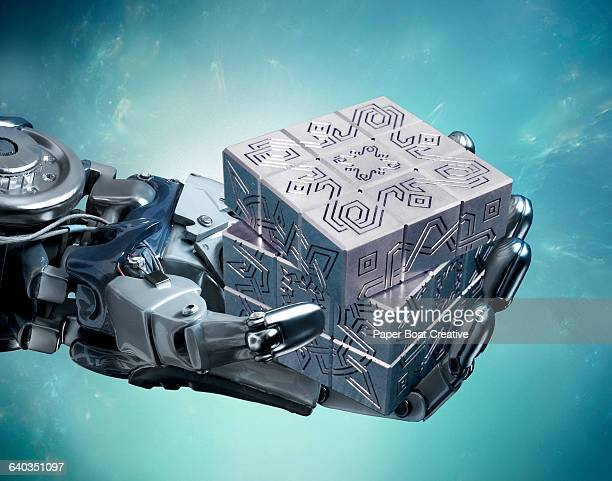 Robot hand holding a metallic cube with puzzles
