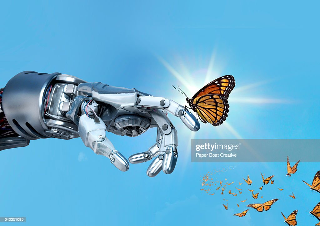 Robot hand holding an orange monarch butterfly : Stock Photo