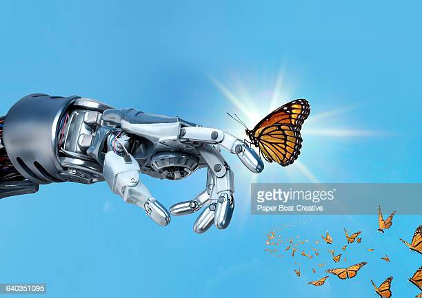 Robot hand holding an orange monarch butterfly