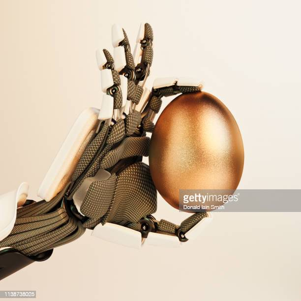 robot hand holding golden egg - greedy smith stock pictures, royalty-free photos & images