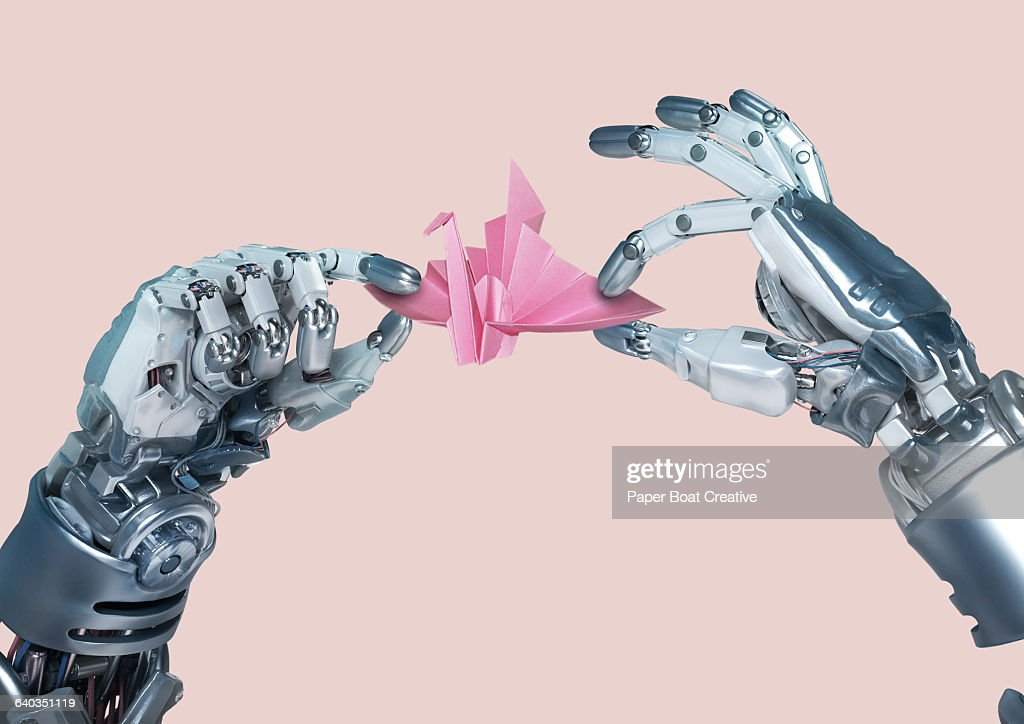 Robot hand making an origami paper crane : Stock Photo