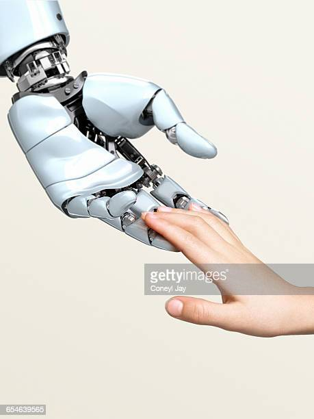 robot hand touching child's fingertips