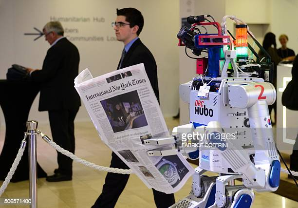 A robot holds a newspaper during a demonstration at the World Economic Forum annual meeting in Davos on January 22 2016 The world must act quickly to...
