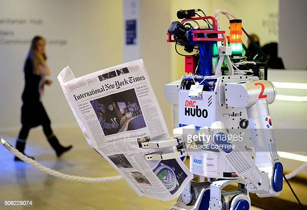A robot holds a newspaper during a demonstration during the World Economic Forum annual meeting in Davos on January 22 2016 The world must act...