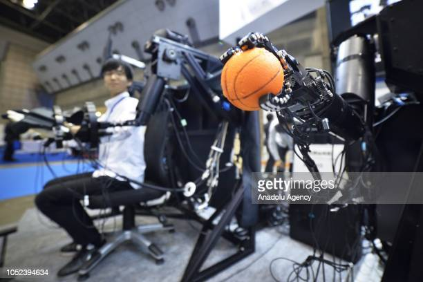 A robot holds a small ball in its hand during a performance of a virtual reality manipulation for humanoid robot at the Japan Robot Week 2018 at...