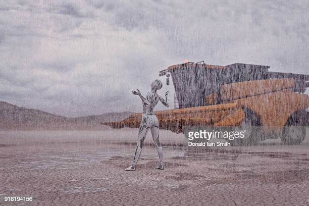 Robot looking up at rain in desert