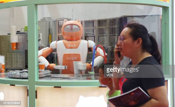 Visitors listen to the concert of Gree's robots band during 2018 World Robot Conference at Beijing Etrong International Exhibition Convention Center...