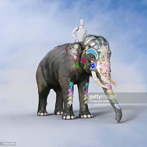 Robot man riding painted elephant