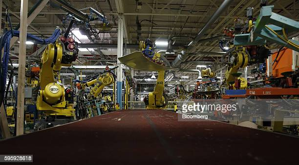 A robot moves a Fiat Chrysler Automobiles NV Town and Country hood at FCA's Sterling Stamping Plant in Sterling Heights Michigan US on Friday Aug 26...