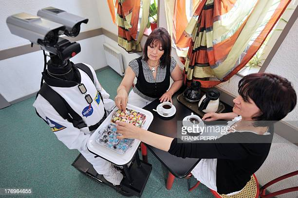 Robot n°1 of First Class Robotics company offers candies to two women on August 7 in Caudan western France This robot the first one of this type in...