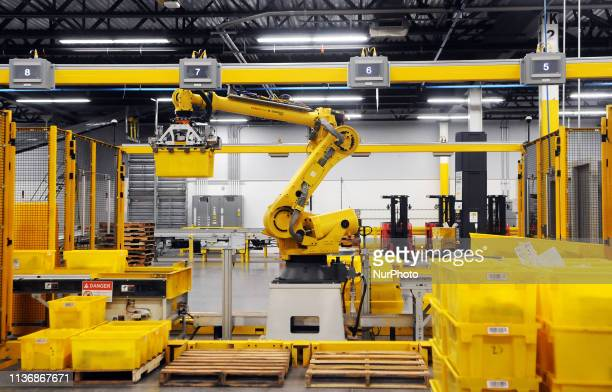 A robot picks up a tote containing product during the first public tour of the newest Amazon Robotics fulfillment center on April 12 2019 in the Lake...