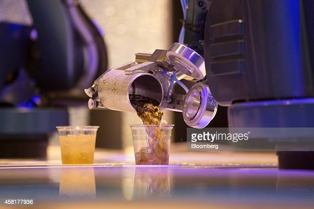 A robot pours a cocktail for a guest in the Bionic Bar onboard the Quantum of the Seas cruise ship operated by Royal Caribbean Cruises Ltd as it sits...