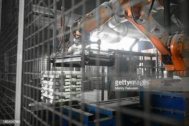 Robot stacking hot ingots in aluminium foundry, low angle view