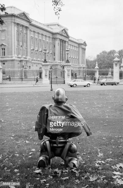 A robot supplied by EMI Records who used them on the cover of the latest album by 'Queen' looking at Buckingham Palace the home of the other Queen...