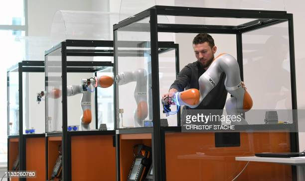 Robot trainer Tobias Jakob manipulates a robot on March 28 2019 at the training college of the robot and equipment manufacturer KUKA at the goup's...