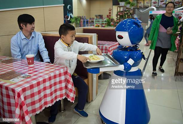 Robot waiters are seen working at a robot restaurant in Kunshan China on May 22 2016 The restaurant has a total of 10 robots in heights of 12 meters...