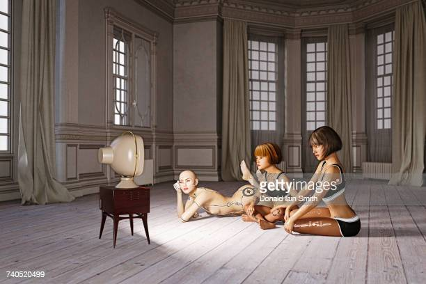 Robot woman and girls laying on floor watching television