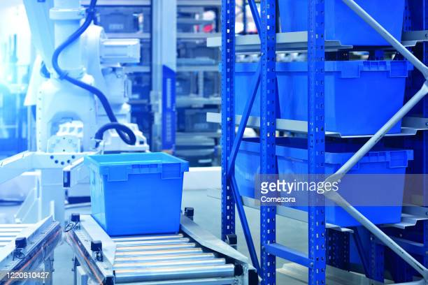 robotic arm carrying crate on shelf - big data storage stock pictures, royalty-free photos & images