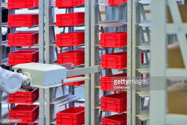 robotic arm carrying merchandise on shelf - big data storage stock pictures, royalty-free photos & images