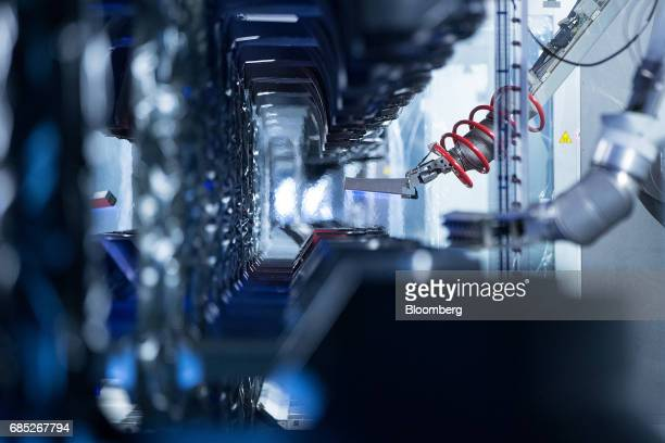 A robotic arm heats plastic automobile bumpers ahead of painting in the Volkswagen AG factory as part of the 'Think Blue' sustainability initiative...
