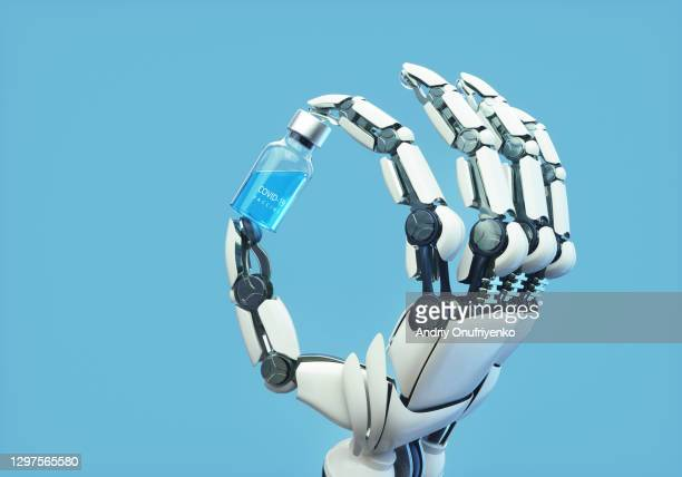 robotic arm holding covid-19 vaccine vial. - robot stock pictures, royalty-free photos & images