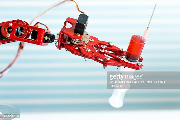 robotic arm holding medical syringe - bloody arm stock photos and pictures
