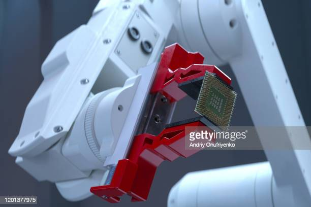 robotic arm holding processor - electrical equipment stock pictures, royalty-free photos & images