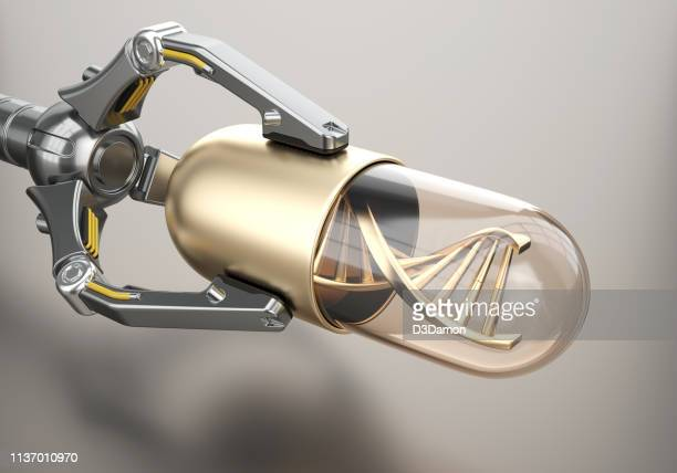 roboterarm hält goldene pille mit dna - medikamenten kapsel stock-fotos und bilder