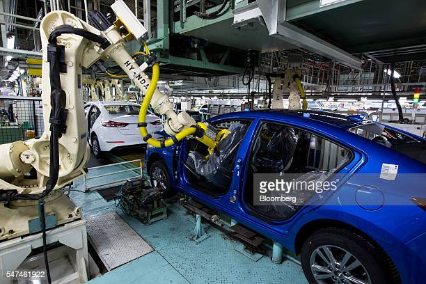 Robotic arm installs a seat in a Hyundai Motor Co. Elantra vehicle on the production line at the company's plant in Ulsan, South Korea, on Monday,...