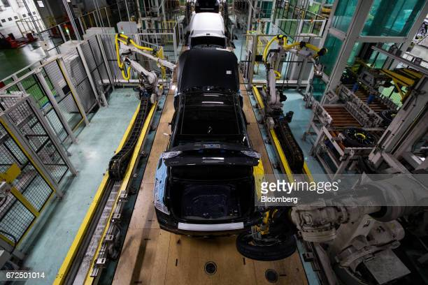 A robotic arm installs a spare tire into a Hyundai Motor Co Genesis luxury sedan on the production line at the company's plant in Ulsan South Korea...