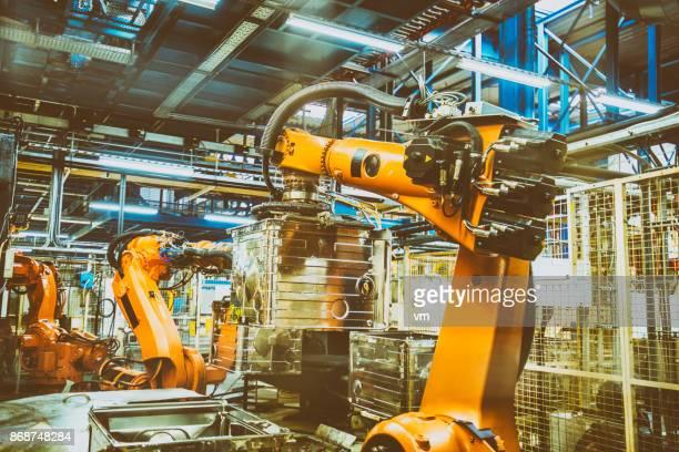 Bras robotisé soulevant pièce de technologie