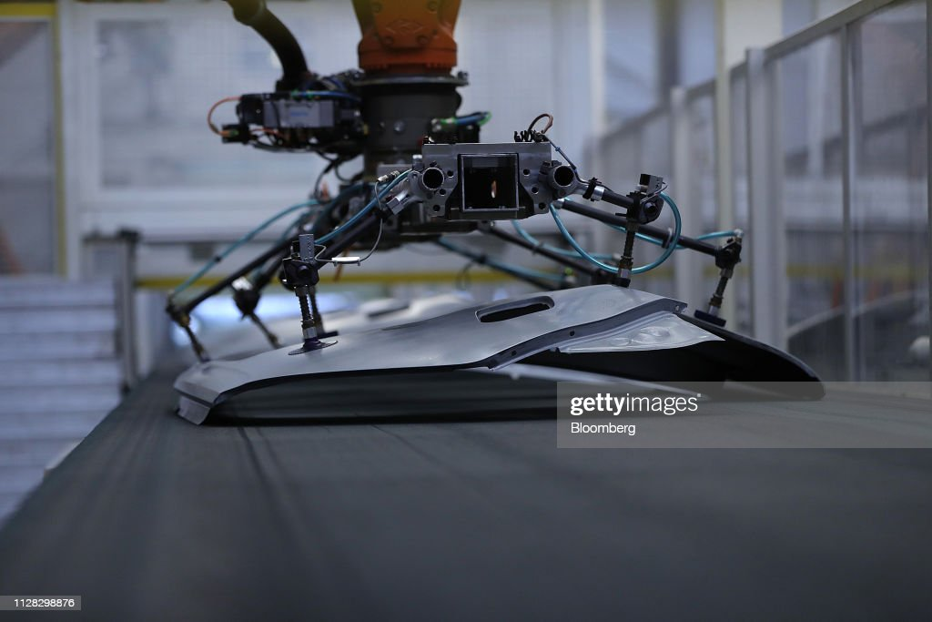 A robotic arm lifts a rear fender panel from a conveyor in the press
