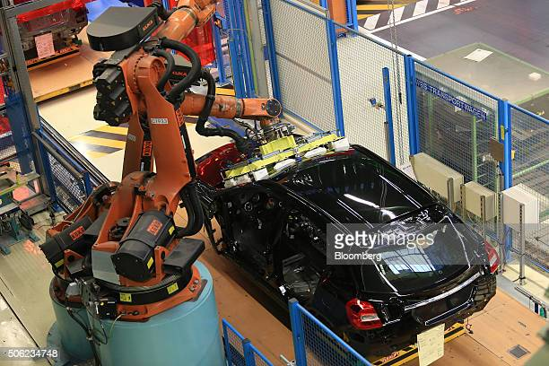 A robotic arm manufactured by Kuka AG fits a windscreen to a MercedesBenz GLA compact SUV automobile produced by Daimler AG on the assembly line at...