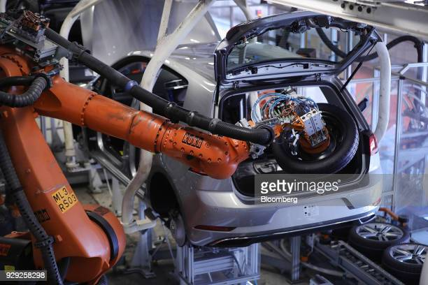 A robotic arm manufactured by Kuka AG places a spare wheel into the trunk of a Volkswagen AG Golf automobile on the production line at the VW factory...