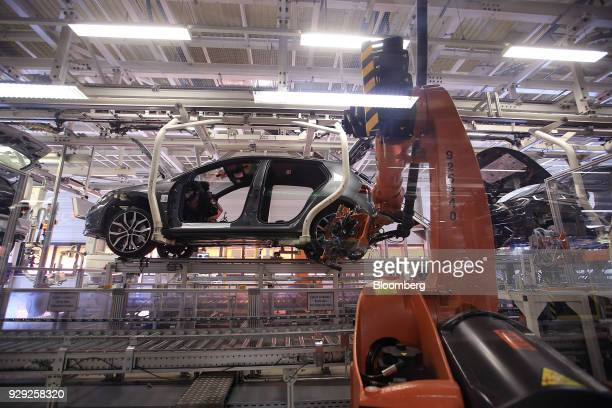 A robotic arm manufactured by Kuka AG secures a wheel to a Volkswagen AG Golf automobile on the production line at the VW factory in Wolfsburg...