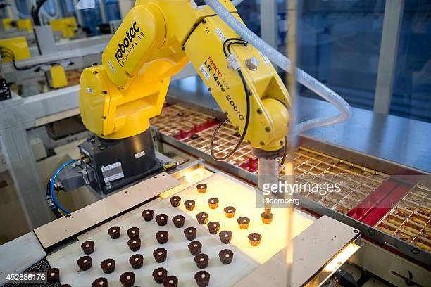 A robotic arm manufactured by Robotec Solutions AG lifts chocolate pralines into packaging on the production line inside the Lindt Spruengli AG...