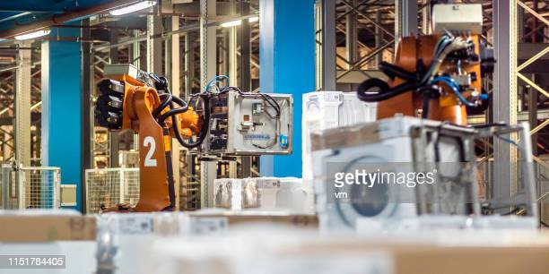robotic arm moving washing machine in a factory - white goods stock pictures, royalty-free photos & images