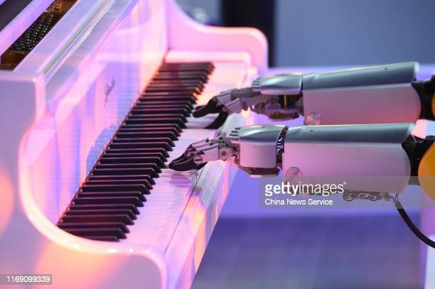A robotic arm of Gree's robotic music band plays the piano on day one of the World Robot Conference 2019 at Beijing Etrong International Exhibition...