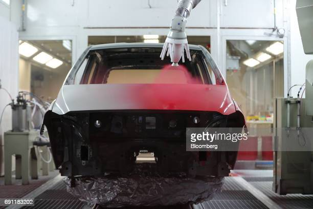 A robotic arm sprays red paint onto an automobile body at PPG Industries Inc's automotive coating's technical center in Ingersheim Germany on...