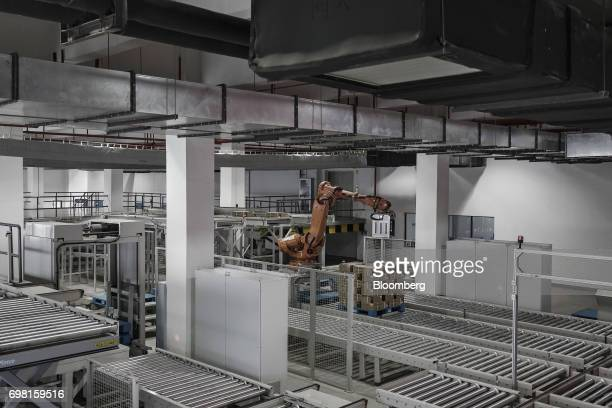 A robotic arm stacks boxes of pharmaceuticals onto a pallet at a China Grand Pharmaceutical and Healthcare Holdings Ltd facility in Wuhan China on...