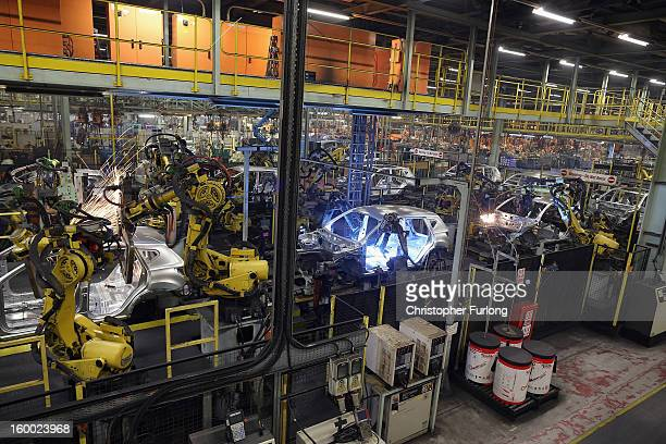Robotic arms assemble and weld the body shell of a Nissan car on the production line at Nissan's Sunderland plant on January 24 2013 in Sunderland...