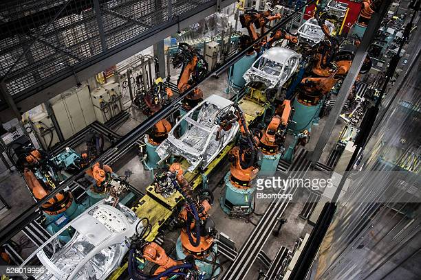 Robotic arms assemble automobile chassis on a production line inside the Mercedes-Benz AG automobile plant, operated by Daimler AG, in Kecskemet,...