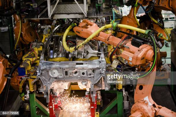 Robotic arms manufactured by ABB Ltd operate on the body shell of a Nissan Micra automobile on the assembly line at the Renault SA factory in Flins...
