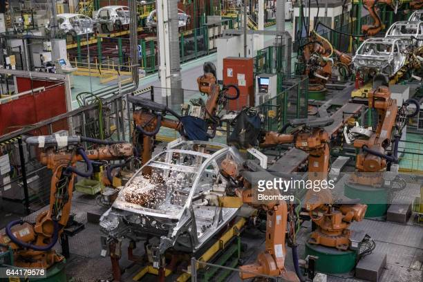 Robotic arms manufactured by ABB Ltd operate on the body shell of a Renault Zoe automobile on the assembly line at the Renault SA factory in Flins...