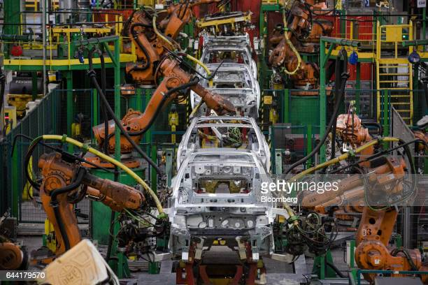 Robotic arms manufactured by ABB Ltd work on the body shells of Renault Clio front and Nissan Micra automobiles on the assembly line at the Renault...