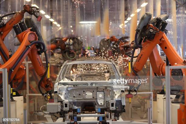 Robotic arms manufactured by Kuka AG operate on a Volkswagen Passat saloon chassis on the automated welding production line inside the VW factory in...